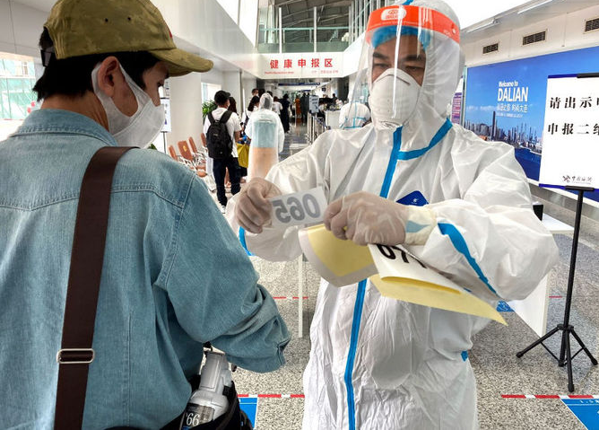 一从飞机上下来,工作人员给乘客贴信息管理的标签
