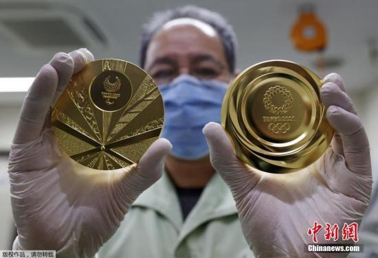 当地时间3月4日,日本大阪,一名工人展示了日本造币厂制作的2020年东京奥运会和残奥会金牌。