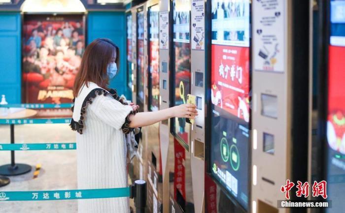 资料图:一位观众在北京万达影城CBD店内自助扫码取票。中新社记者 贾天勇 摄