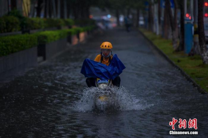 """台风""""森拉克""""掠过海南三亚,琼岛泛起强降雨天气。图为暴雨导致海口部门路段泛起积水,外卖小哥冒险通过积水路段。 骆云飞 摄"""