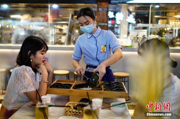 资料图:7月29日晚,云南昆明,一餐饮店服务员正在为顾客服务。 中新社记者 康平 摄