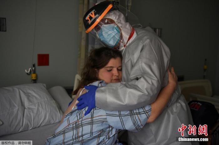 资料图:58岁的约瑟夫·瓦隆医生是美国联合纪念医疗中心的首席医疗官,他与43岁的护士克里斯蒂娜·马瑟斯在病房内拥抱。