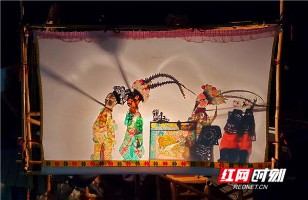 村里人闲坐着欣赏灯光的照片 湖南皮影戏