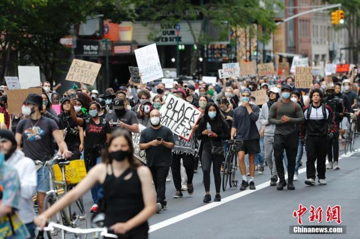 资料图:当地时间6月1日,美国纽约民众在曼哈顿街道游行抗议警察暴力执法。5月24日,明尼苏达州明尼阿波利斯市,非裔美国人弗洛伊德因警察在执法过程中涉嫌动作失当而身亡。此事件在全美引发示威浪潮。中新社记者 廖攀 摄