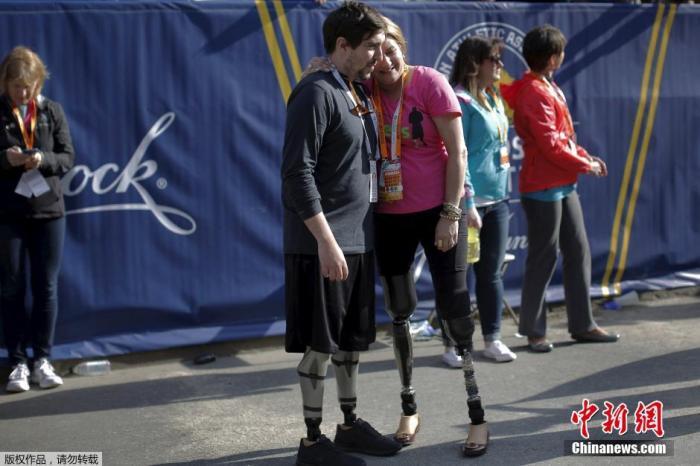 资料图:当地时间2016年4月18日,美国波士顿马拉松比赛开跑。两位爆炸案受害者相拥,他们都在此前的爆炸案中失去双腿。