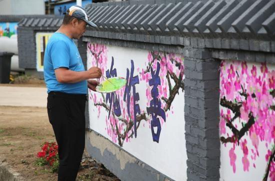 敦化市文联组织文艺志愿者为孝心村义务绘制文化墙