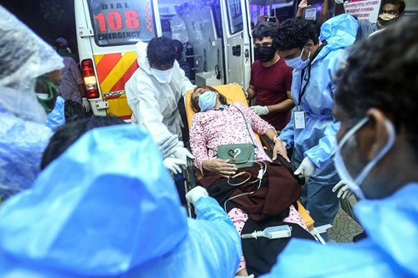 8月7日,在印度喀拉拉邦科泽科德一家医院,医护人员用担架运送伤员。新华社 图