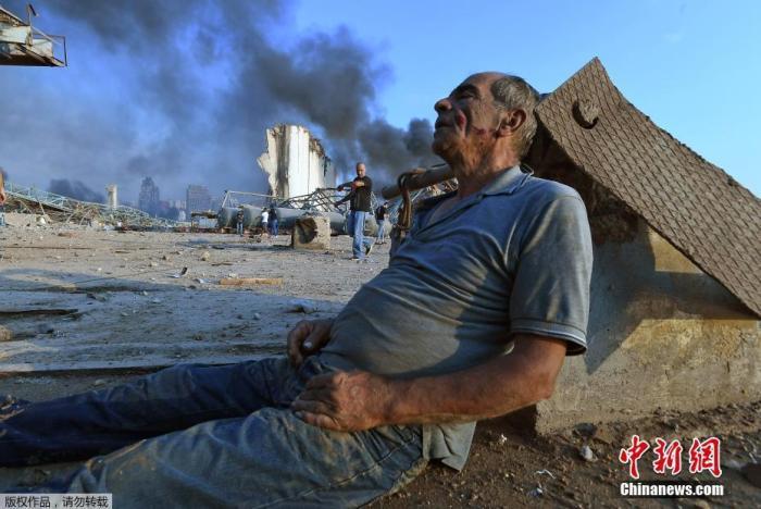 当地时间8月4日晚,黎巴嫩首都贝鲁特港口区发生剧烈爆炸。图为伤者坐在路边等待救援。