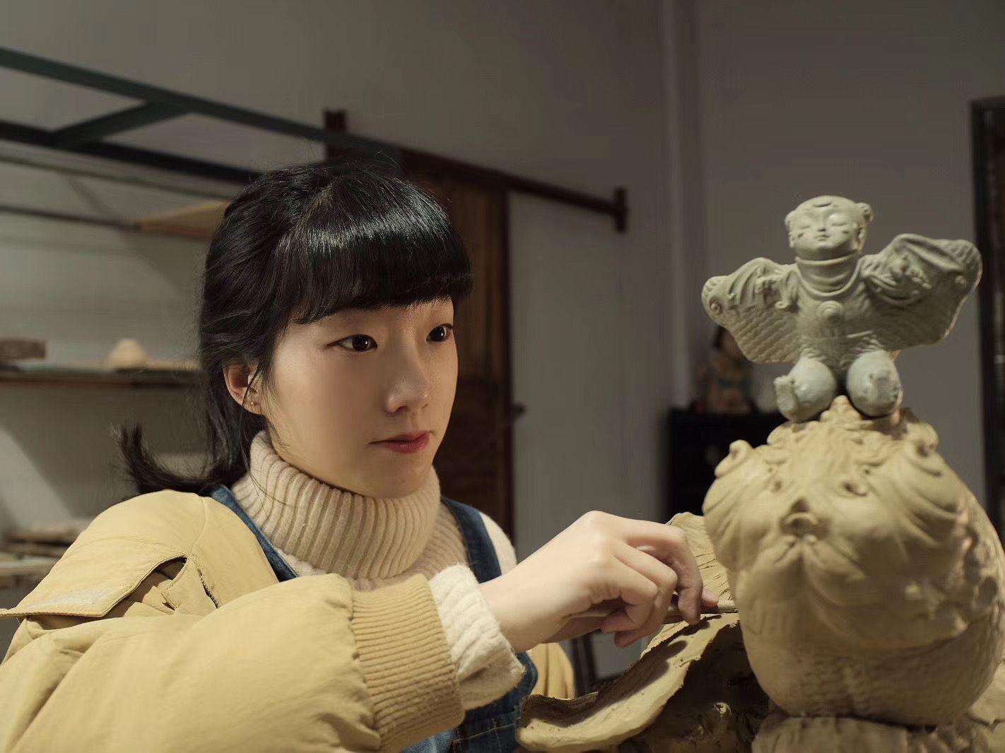 王小丹手持竹刀正在泥塑,摄于2019年12月。 供访者受图。