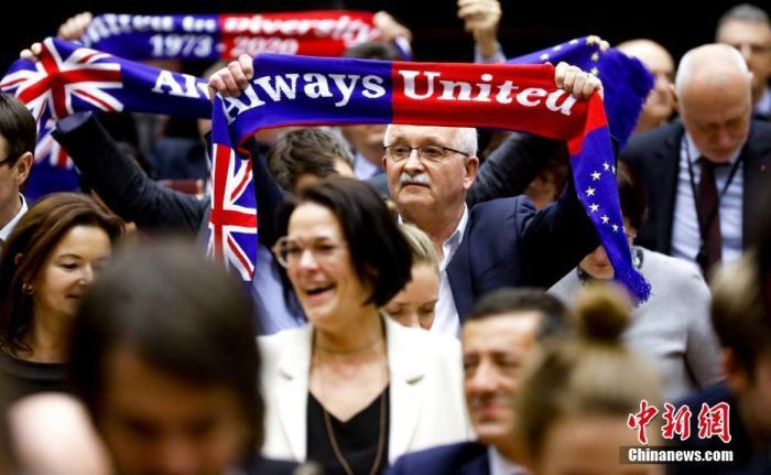 """当地时间1月29日,欧洲议会批准""""脱欧""""协议。图为投票结束后,在场议员高举""""永远团结""""旗帜。中新社发 欧盟供图"""