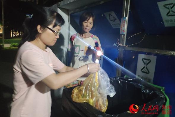 督导员王姐拿动手电筒,引导住民垃圾分类。 人民网樊欢迪 摄