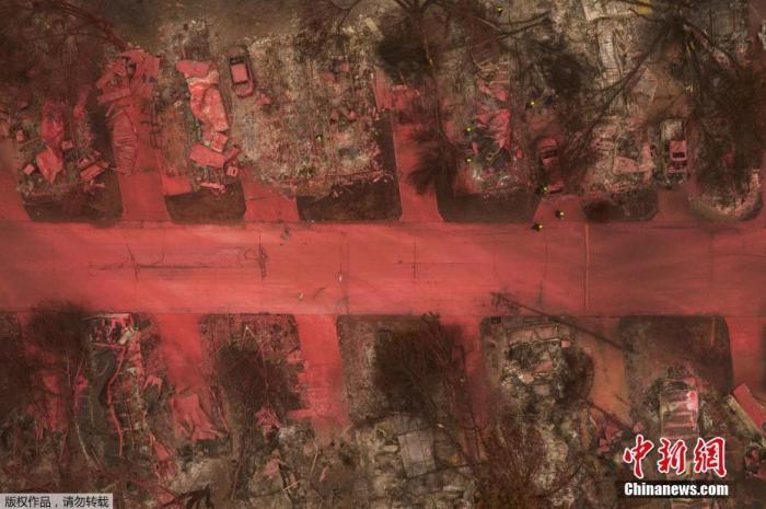 资料图:当地时间9月13日,美国俄勒冈州,当地消防喷洒红色阻燃剂扑灭阿尔梅达山火,大片的地面、多辆汽车、房屋、植被都被染红,搜救人员在废墟中寻找遇难者。