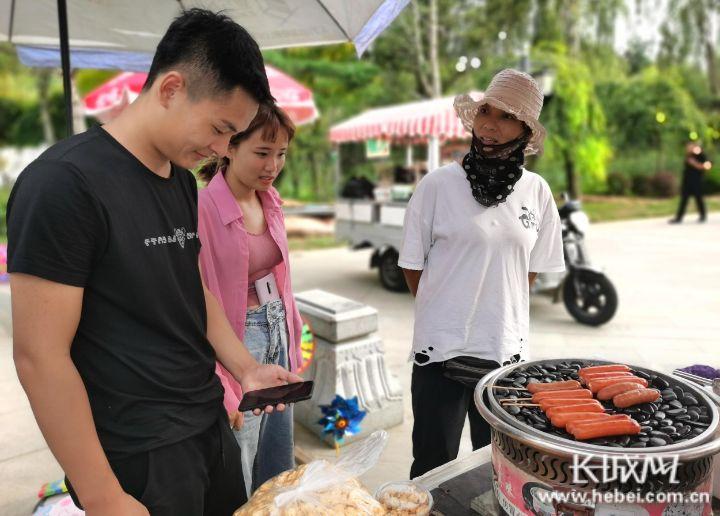 高玉芹(右一)在向旅客先容商品。长城网记者 郭庆敏 摄