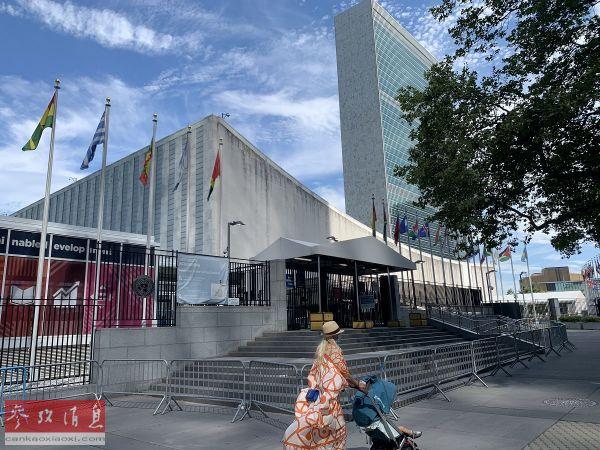 资料图片:7月20日,一名推童车的女子经过位于纽约的联合国总部游客入口处。(新华社记者 王建刚 摄)