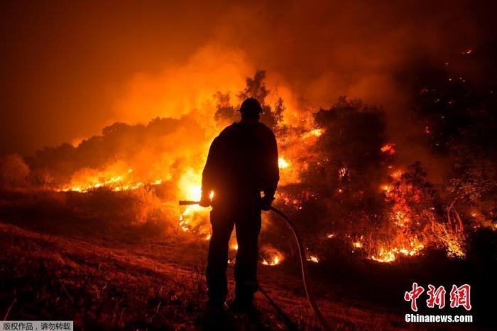 资料图:当地时间9月15日,美国加州,消防员站在消防车上观看山猫大火在蒙罗维亚房屋后的山坡上燃烧。