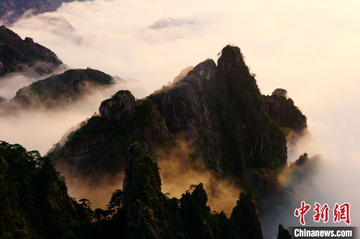 18日傍晚,黄山云海翻腾 青褐色的山峰矗立其间。 方玮 摄