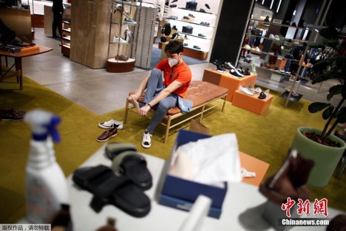 资料图:意大利米兰一家商店内,一名男子在试穿鞋子。