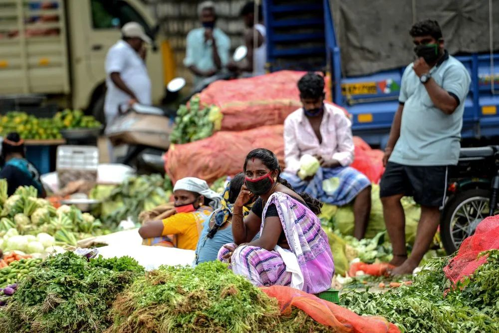 9月11日,戴口罩的摊贩们在印度金奈的伯勒沃勒姆集市等待顾客。