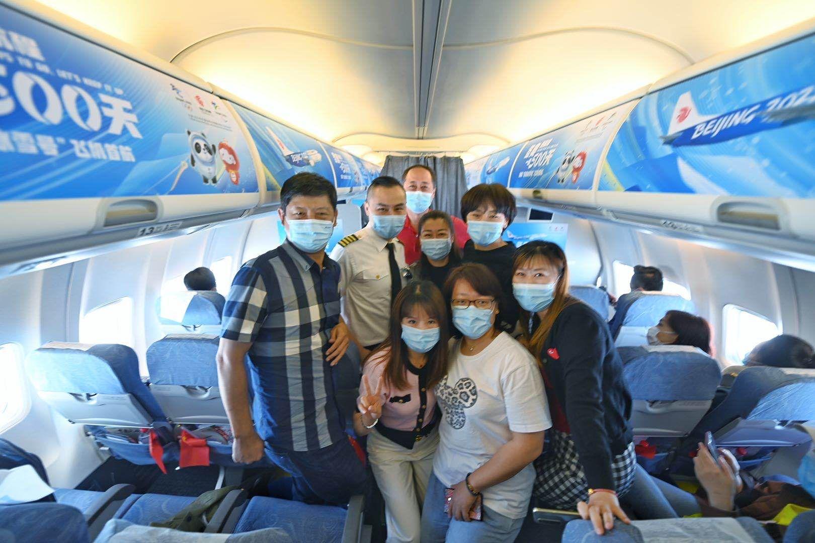 航班上举行了特殊的欢迎活动,旅客们与机组人员合影。新京报记者 陶冉 摄