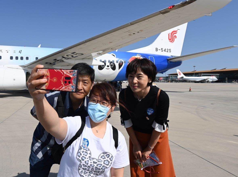 """""""冬奥冰雪号""""航班的旅客拍照合影。 新京报记者 陶冉 摄"""