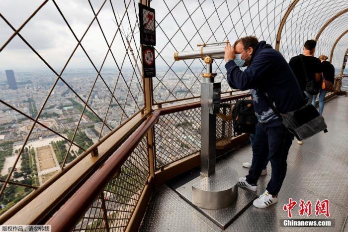 资料图:当地时间7月15日,法国巴黎埃菲尔铁塔顶层开放,一名男子通过望远镜俯瞰巴黎。