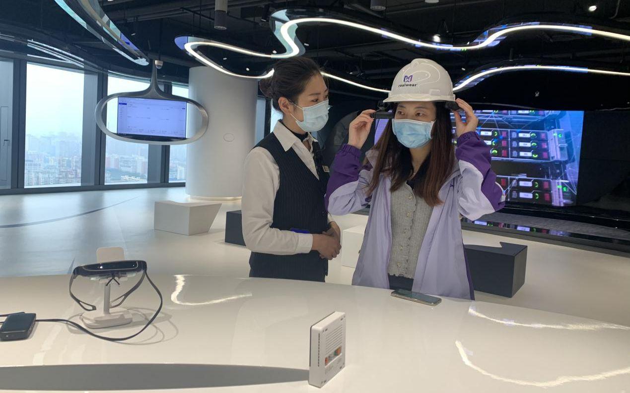在丽泽SOHO的5G实行室,观光者在事情职员指导下体验5G应用场景。丰台区委宣传部供图