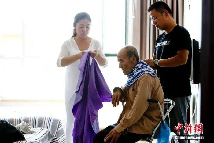 资料图:养老院事情职员照护老人。中新社发 陆欣 摄