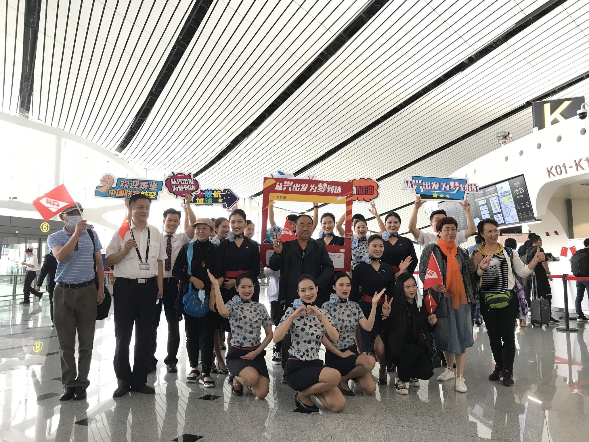 """""""进博号""""飞机的游客抵达大兴机场,在机场和空乘职员合影。东航供图"""