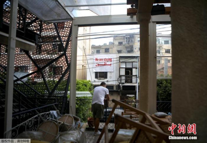 当地时间8月13日,黎巴嫩贝鲁特的一处居民区,一名男子在清理满是瓦砾的公寓。