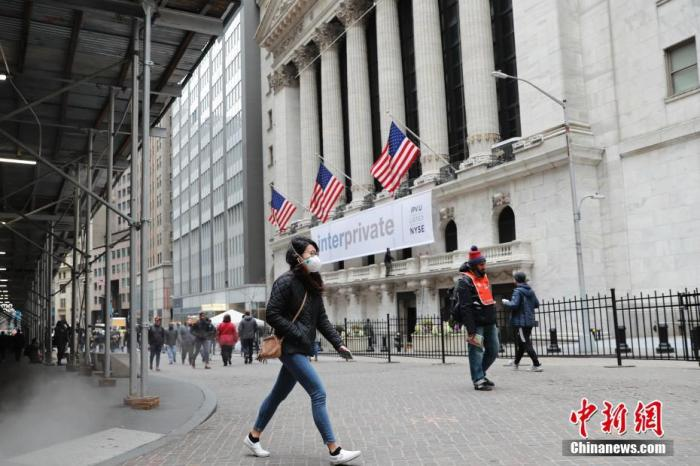 当地时间3月12日,一位戴口罩的民众走过纽约证券交易所。 中新社记者 廖攀 摄