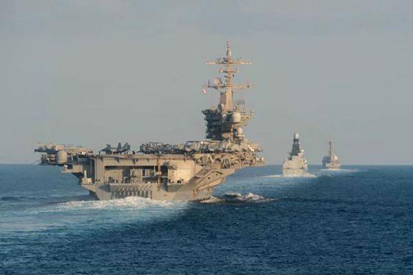 """这张美国海军提供的照片显示,2019年11月19日,美国""""亚伯拉罕·林肯""""号航母(左)、英国皇家海军""""保卫者""""号驱逐舰(中),美国海军""""法拉格特""""号导弹驱逐舰(右)编队通过霍尔木兹海峡。新华社/美联"""