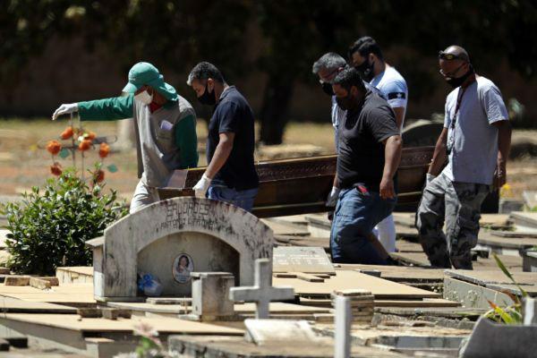 9月3日,在巴西首都巴西利亚,工作人员搬运一位新冠死亡患者的遗体。新华社/美联