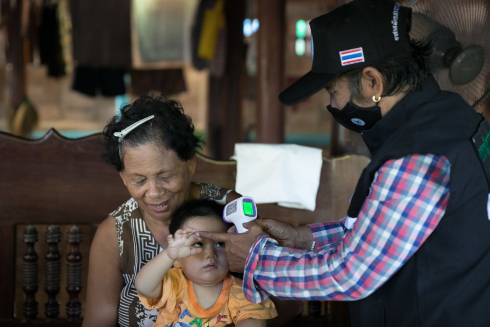 6月24日,泰国西部叻武里府邦沛县的乡村医疗志愿者瑙瓦拉(右)为一名儿童测量体温。 新华社记者 张可任摄
