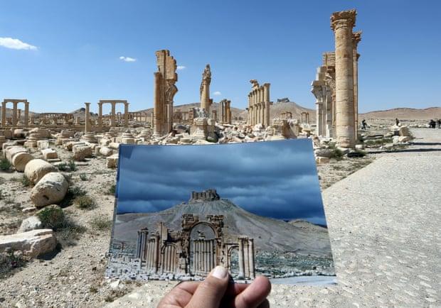 """2016年,在被""""伊斯兰国""""摧毁的巴尔米拉凯旋门前拍摄的照片,其手持的是2014年拍摄于同一地点的风景的照片。"""