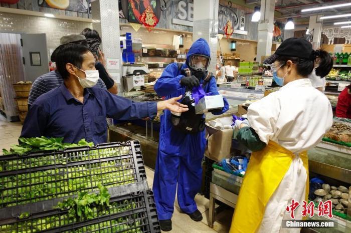 资料图:当地时间9月7日,一位市民身着防护服头戴防护面具在纽约皇后区一家超市为顾客发手套、口罩等抗疫物资。 中新社记者 廖攀 摄