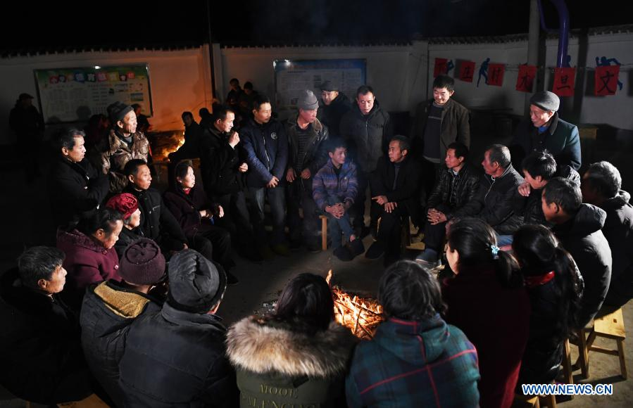 Mao Xianglin and villagers discuss the sales plan of oranges at Xiazhuang Village, Zhuxian Township, Wushan County of southwest China's Chongqing, in the evening of Jan. 6, 2021. For those who lived in Xiazhuang Village, it once took them two days to reach the nearest county. Thanks to the unceasing efforts of Mao Xianglin, the onerous travelling has become a history. In 1997, 38-year-old Mao Xianglin, the secretary of Communist Party of China (CPC) branch of Xiazhuang Village and head of the village committee, mobilized the villagers to build a better road to the outside world. To speed up the road building, Mao once worked and lived at the construction site for three months without going home. Finally in 2004, an 8-kilometer long and 2-meter wide road was finished. After more widening and hardening work conducted by the local government, the travel time from Xiazhuang Village to the county seat has been slashed to about one and a half hours. For Mao, building a road is the first step, and seeking a way to prosperity is the second. After consulting experts, he decided to develop orange planting industry in the village. Now, the orange orchard here covers an area of about 650 mu (about 43.3 hectares), and the whole village has shaken off poverty in 2015.