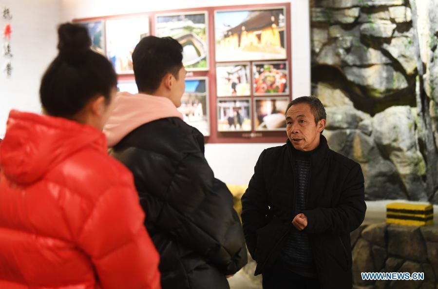 Mao Xianglin (R) introduces the story of building roads in Xiazhuang Village to the audience at an exhibition hall at Xiazhuang Village, Zhuxian Township, Wushan County of southwest China's Chongqing, Jan. 6, 2021. For those who lived in Xiazhuang Village, it once took them two days to reach the nearest county. Thanks to the unceasing efforts of Mao Xianglin, the onerous travelling has become a history. In 1997, 38-year-old Mao Xianglin, the secretary of Communist Party of China (CPC) branch of Xiazhuang Village and head of the village committee, mobilized the villagers to build a better road to the outside world. To speed up the road building, Mao once worked and lived at the construction site for three months without going home. Finally in 2004, an 8-kilometer long and 2-meter wide road was finished. After more widening and hardening work conducted by the local government, the travel time from Xiazhuang Village to the county seat has been slashed to about one and a half hours. For Mao, building a road is the first step, and seeking a way to prosperity is the second. After consulting experts, he decided to develop orange planting industry in the village. Now, the orange orchard here covers an area of about 650 mu (about 43.3 hectares), and the whole village has shaken off poverty in 2015.