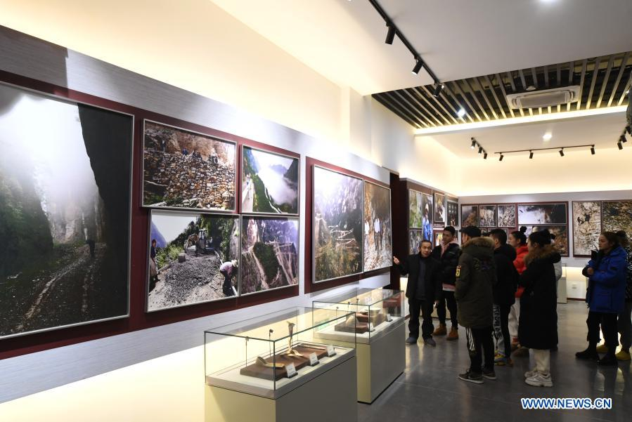Mao Xianglin (1st, L) introduces the story of building roads in Xiazhuang Village to the audience at an exhibition hall at Xiazhuang Village, Zhuxian Township, Wushan County of southwest China's Chongqing, Jan. 6, 2021. For those who lived in Xiazhuang Village, it once took them two days to reach the nearest county. Thanks to the unceasing efforts of Mao Xianglin, the onerous travelling has become a history. In 1997, 38-year-old Mao Xianglin, the secretary of Communist Party of China (CPC) branch of Xiazhuang Village and head of the village committee, mobilized the villagers to build a better road to the outside world. To speed up the road building, Mao once worked and lived at the construction site for three months without going home. Finally in 2004, an 8-kilometer long and 2-meter wide road was finished. After more widening and hardening work conducted by the local government, the travel time from Xiazhuang Village to the county seat has been slashed to about one and a half hours. For Mao, building a road is the first step, and seeking a way to prosperity is the second. After consulting experts, he decided to develop orange planting industry in the village. Now, the orange orchard here covers an area of about 650 mu (about 43.3 hectares), and the whole village has shaken off poverty in 2015.