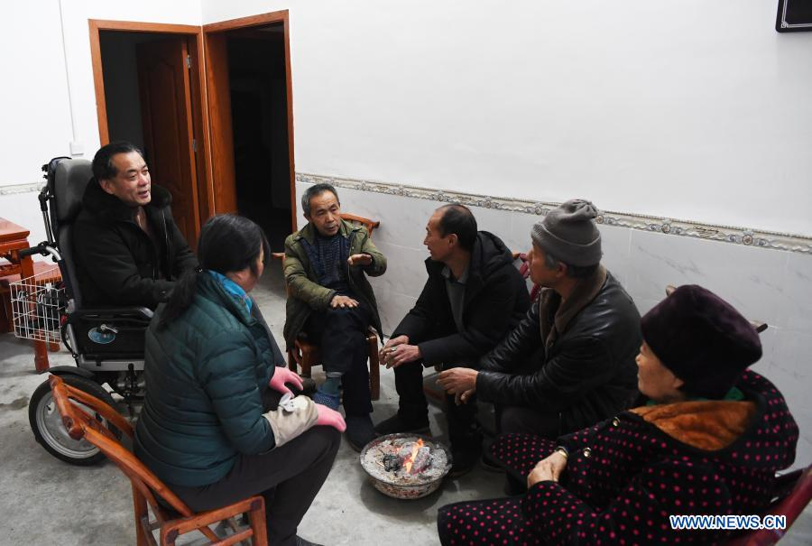 Mao Xianglin (3rd, L) talks with villagers at Xiazhuang Village, Zhuxian Township, Wushan County of southwest China's Chongqing, Jan. 6. 2021. For those who lived in Xiazhuang Village, it once took them two days to reach the nearest county. Thanks to the unceasing efforts of Mao Xianglin, the onerous travelling has become a history. In 1997, 38-year-old Mao Xianglin, the secretary of Communist Party of China (CPC) branch of Xiazhuang Village and head of the village committee, mobilized the villagers to build a better road to the outside world. To speed up the road building, Mao once worked and lived at the construction site for three months without going home. Finally in 2004, an 8-kilometer long and 2-meter wide road was finished. After more widening and hardening work conducted by the local government, the travel time from Xiazhuang Village to the county seat has been slashed to about one and a half hours. For Mao, building a road is the first step, and seeking a way to prosperity is the second. After consulting experts, he decided to develop orange planting industry in the village. Now, the orange orchard here covers an area of about 650 mu (about 43.3 hectares), and the whole village has shaken off poverty in 2015.