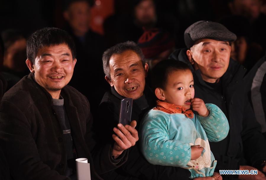 Mao Xianglin (2nd, L) and villagers watch a performance organized by the cultural center of Wushan County at Xiazhuang Village, Zhuxian Township, Wushan County of southwest China's Chongqing, Jan. 6, 2021. For those who lived in Xiazhuang Village, it once took them two days to reach the nearest county. Thanks to the unceasing efforts of Mao Xianglin, the onerous travelling has become a history. In 1997, 38-year-old Mao Xianglin, the secretary of Communist Party of China (CPC) branch of Xiazhuang Village and head of the village committee, mobilized the villagers to build a better road to the outside world. To speed up the road building, Mao once worked and lived at the construction site for three months without going home. Finally in 2004, an 8-kilometer long and 2-meter wide road was finished. After more widening and hardening work conducted by the local government, the travel time from Xiazhuang Village to the county seat has been slashed to about one and a half hours. For Mao, building a road is the first step, and seeking a way to prosperity is the second. After consulting experts, he decided to develop orange planting industry in the village. Now, the orange orchard here covers an area of about 650 mu (about 43.3 hectares), and the whole village has shaken off poverty in 2015.
