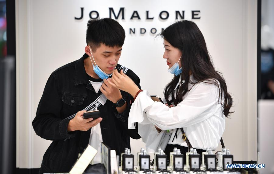A customer selects perfume products at a duty-free shop in Haikou, capital of south China's Hainan Province Jan. 7, 2021. Offshore duty-free shops in China's island province of Hainan have raked in more than 32 billion yuan (about 4.9 billion U.S. dollars) in sales in 2020. (Xinhua/Guo Cheng)
