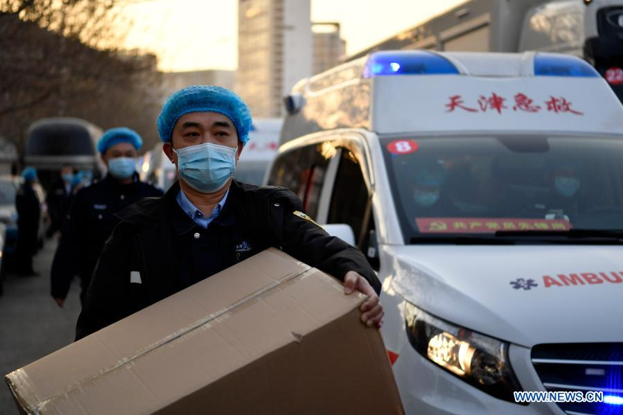 Members of a medical team load supplies on vehicles at Tianjin Emergency Center in Tianjin, north China, Jan. 11, 2021. As the second wave of medical emergency aid from Tianjin to Hebei Province, the team consists of 87 members, flanked by 20 ambulances and two other vehicles loaded with supplies for epidemic prevention and control. (Xinhua/Li Ran)