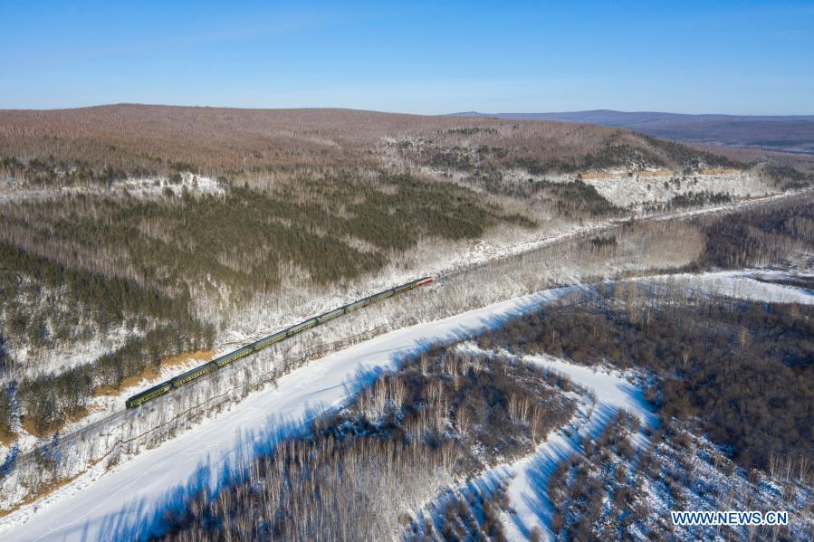 Aerial photo taken on Jan. 11, 2021 shows a train running through a forest in a scenic spot in Mohe City, northeast China's Heilongjiang Province. (Xinhua/Xie Jianfei)