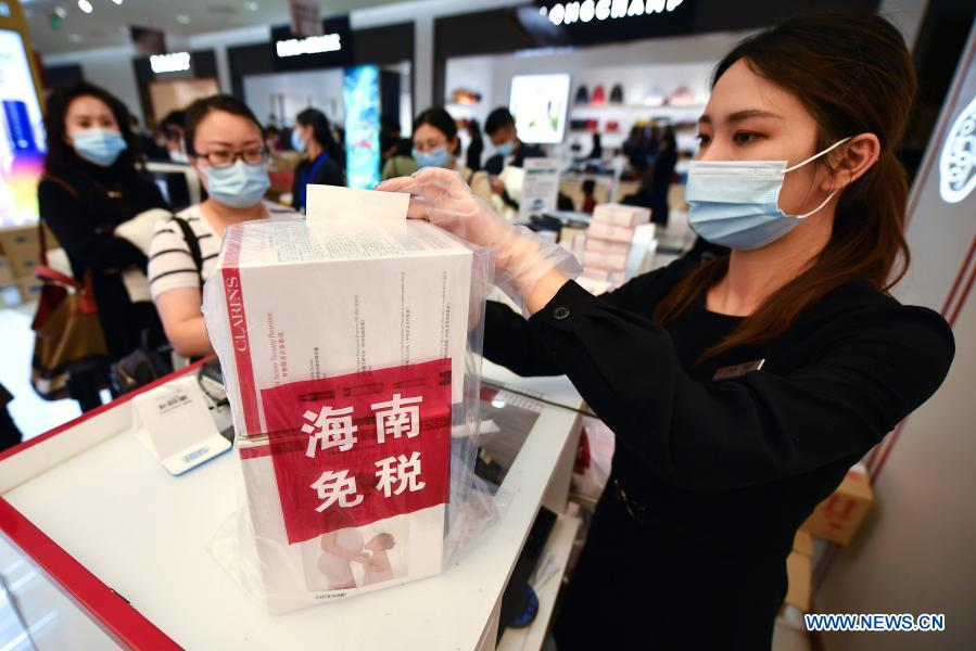 A sales assistant packs purchased products at a duty-free shop in Haikou, capital of south China's Hainan Province Jan. 7, 2021. Offshore duty-free shops in China's island province of Hainan have raked in more than 32 billion yuan (about 4.9 billion U.S. dollars) in sales in 2020. (Xinhua/Guo Cheng)