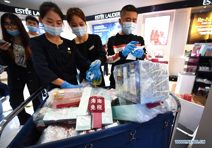 Sales assistants arrange purchased products at a duty-free shop in Haikou, capital of south China's Hainan Province Jan. 7, 2021. Offshore duty-free shops in China's island province of Hainan have raked in more than 32 billion yuan (about 4.9 billion U.S. dollars) in sales in 2020. (Xinhua/Guo Cheng)