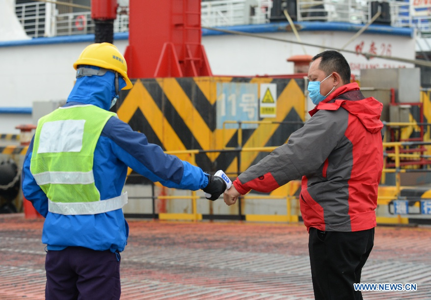 A member of ship crew checks a passenger's body temperature before boarding at Xinhai Port in Haikou, capital of south China's Hainan Province, Jan. 11, 2021. More people flock to Hainan to evade cold weather as air temperature dropped dramatically in most parts of China over the past few days. Intensified pandemic prevention and control measures including body temperature check and passenger information confirmation have been adopted at airports and seaports in Haikou. (Xinhua/Zhou Jiayi)