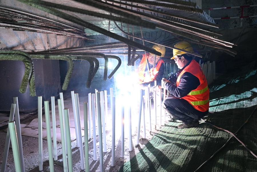 Workers work at the construction site of a grand bridge of the Fuzhou-Xiamen high-speed railway at Qingkou Town of Minhou County, southeast China's Fujian Province, Jan. 12, 2021. The 14,500-tonne girder, a part of the 896-meter grand bridge, was successfully swiveled to the targeted position on Tuesday. (Xinhua/Lin Shanchuan)