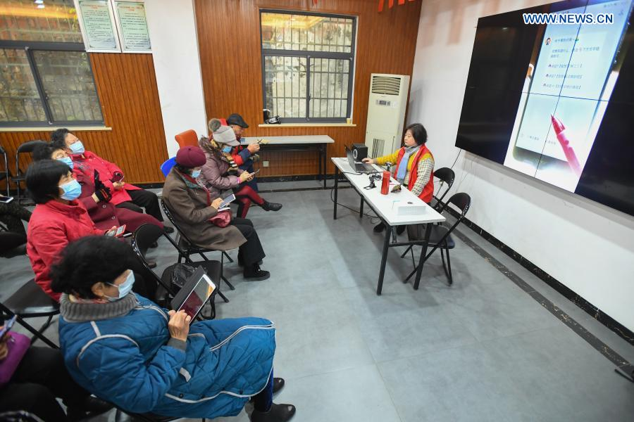 A volunteer teaches elders how to play WeChat on smartphone at Xiajiachong community in Tianxin District of Changsha City, central China's Hunan Province, Jan. 12, 2021. The community has invited volunteers to teach the use of smartphone to elders, helping them keep pace with modern society. (Xinhua/Chen Zeguo)