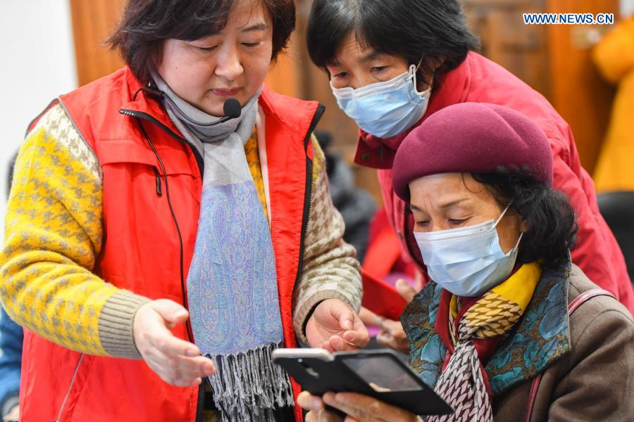 A volunteer teaches the use of smartphone to elders at Xiajiachong community in Tianxin District of Changsha City, central China's Hunan Province, Jan. 12, 2021. The community has invited volunteers to teach the use of smartphone to elders, helping them keep pace with modern society. (Xinhua/Chen Zeguo)