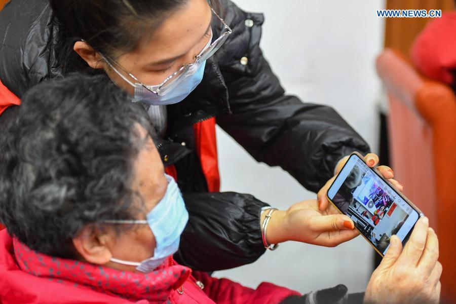 A volunteer teaches an elder how to film and view video with smartphone at Xiajiachong community in Tianxin District of Changsha City, central China's Hunan Province, Jan. 12, 2021. The community has invited volunteers to teach the use of smartphone to elders, helping them keep pace with modern society. (Xinhua/Chen Zeguo)
